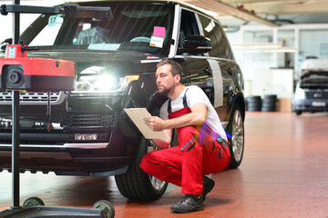 car repair shop - worker checks and adjusts the headlights of a car's lighting system