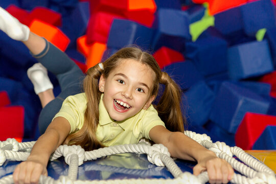 Excited girl climbing rope ladder over soft cube pit at indoor playground, overhead view