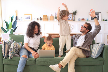 Young beautiful happy family relaxing on the sofa and look at the laptop at home.