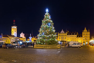 Ceske Budejovice, Czech Republic. Christmas tree at Christmas market on Premysl Otakar II Square in night. The Black Tower, St Nicholas Cathedral and Samson fountain are visible in the background.