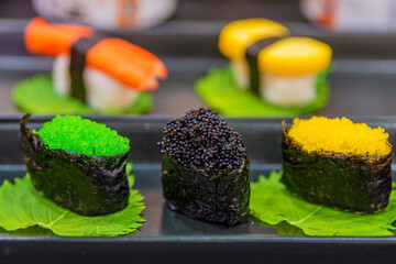 Photo sur Plexiglas Roe An Image of Hand-Rolled Sushi. Sushi Black fish roe, Green fish roe, Yellow fish roe and Background blur Sushi set. Selective Focus