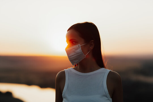 Girl wearing a face mask outside during the Coronavirus, COVID-19, virus pandemic. Close up of girl using surgical mask and looking away during a colorful sunset. Copy space.