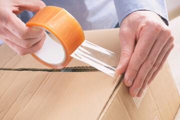 Hand taping the cardboard box