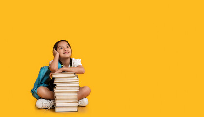 Chinese School Girl Sitting At Books Stack On Yellow Background