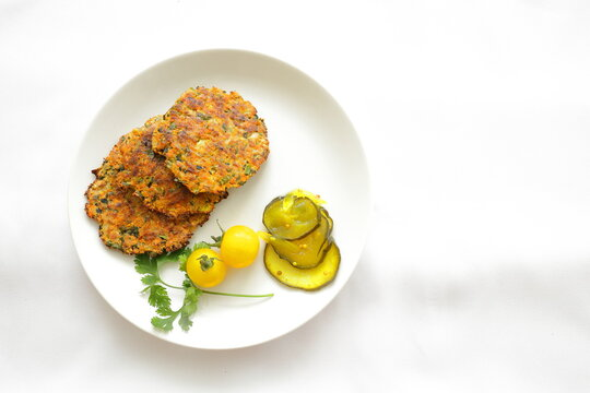 Healthy zucchini patties on a white plate with pickles and tomatoes.