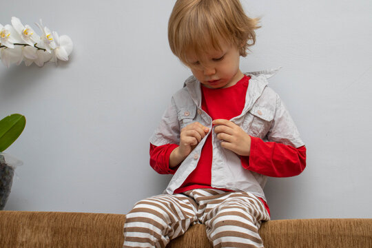 Childhood independence concept ,little boy buttoning on shirt, fastening his buttons , on white gray background. The child puts on his own clothes