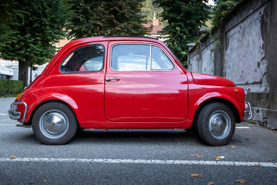 Red old vintage Fiat Nuova 500, this vehicle was a cheap town car produced by the Italian manufacturer Fiat between 1957 and 1975. Valsesia / Italy - September 06, 2020