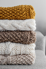 Detail of a stack of five woolen blankets of various colors beige, bro