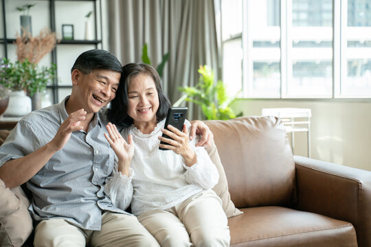 Social distancing or new normal concept.Senior asian couple sitting on sofa in home playing smartphone and video conference with grandchild.They are smiling to spend their time together with happiness
