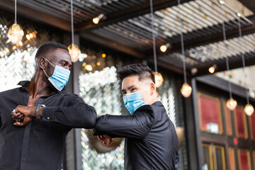 African American black man and Asian friend wearing protective face mask elbow bump greeting for...