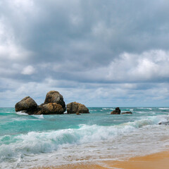 Beautiful sea scape. Sandy beach and boulders.