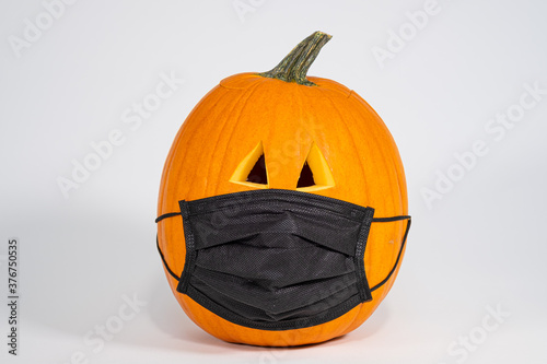 Carved Halloween pumpkin wearing a Covid 19 face mask isolated on a white background
