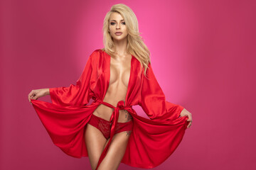 Young slim woman in red bathrobe smiling on a pink background in the studio. Sexy girl with...