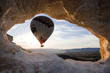 Hot air balloon framed between rock formation at sunrise, Goreme National Park, Cappadocia, Anatolia, Turkey