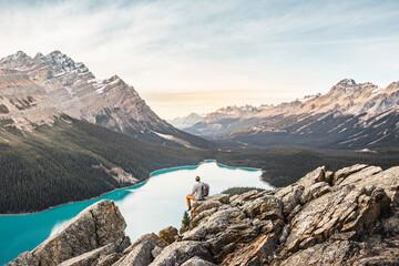 Man sitting, looking at view, viewpoint overlooking Peyto Lake, Lake Louise, Alberta, Canada