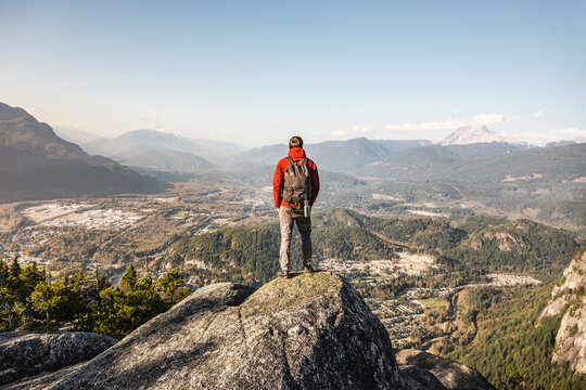 Man standing on mountain, looking at view, Stawamus Chief, overlooking Howe Sound Bay, Squamish, British Columbia, Canada