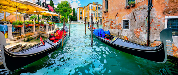 Wharf with gondolas by cafe on Grand Canal. Venice, Italy