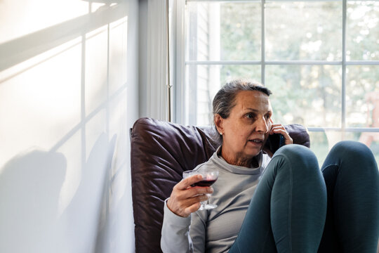 Senior woman talking on smartphone while holding glass of wine at home