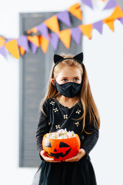 A girl in a Halloween costume with a mask on is holding a pumpkin filled with treats during the covid19 pandemic at a fall festival.