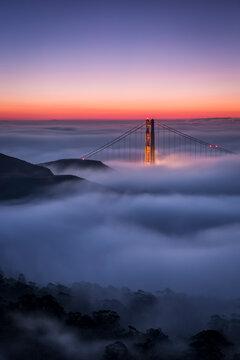 Scenic view of fog over Golden Gate Bridge at sunrise