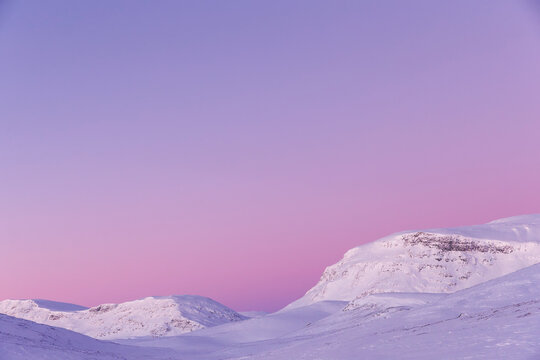 View of snowy landscape against sky during sunset