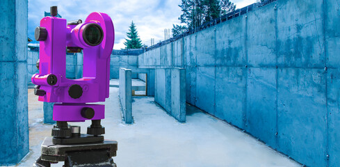 Wall Murals Lilac Surveyor tool on the construction site. Geodetic works in construction. Theodolite of lilac color on the background of the concrete frame of the house. Monitoring the progress of construction.