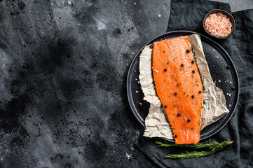 Fresh salmon fillet with salt, herbs and spices. Black background. Top view. Copy space