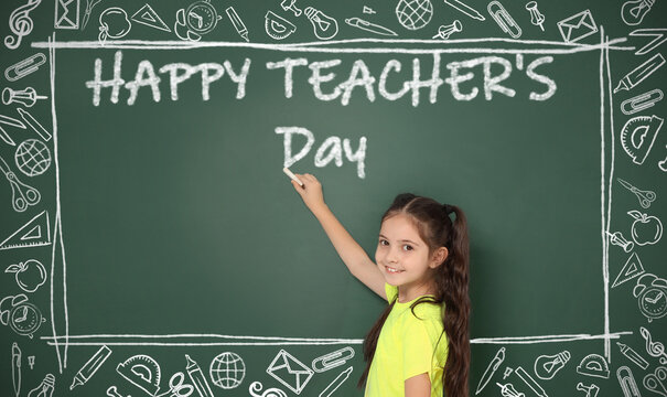 Cute little girl writing phrase Happy Teacher's Day on chalkboard