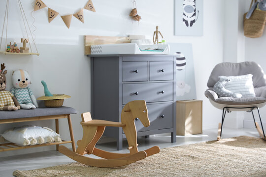 Beautiful baby room interior with toys, rocking chair and modern changing table