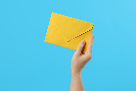 Woman holding yellow paper envelope on light blue background, closeup