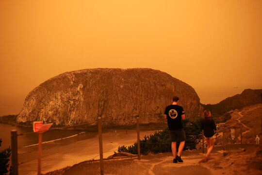 People walk by the Pacific Ocean coast as smoke from wildfires covers an area near Seal Rock, Oregon