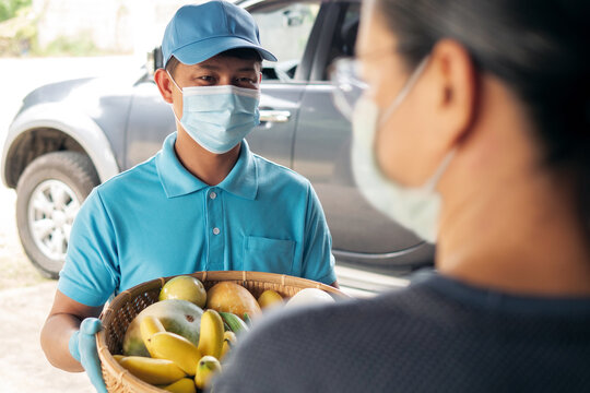 Delivery man wearing face mask and protective gloves delivering fresh fruits and vegetables in bamboo basket from organic farm to senior people home in Coronavirus (COVID-19) pandemic.