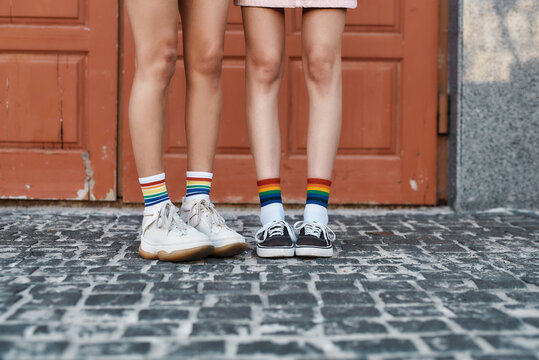 Close up of legs of young female couple wearing rainbow colored socks, standing together in front of the door outdoors