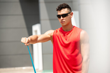 Handsome sports man doing shoulder front raise exercise with elastic resistance band outdoors - home open air workout concept