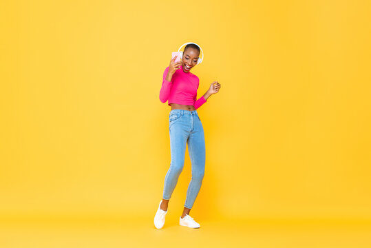 Joyful portrait of dancing happy African American woman wearing headphones listening to music from smartphone on colorful yellow studio isolated background