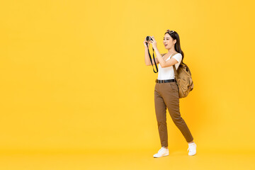 Young Asian tourist woman taking photo with camera isolated on yellow background