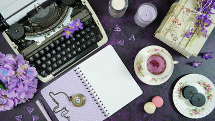 Purple theme vintage writers desktop workspace with typewriter, lavendar tea, hibiscus flowers and old books on stylish purple textured background. Top view blog hero header creative flat lay.