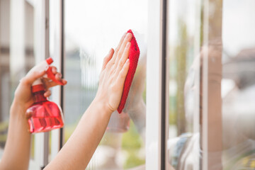 housework and housekeeping concept . Woman in gloves cleaning window with rag and cleanser spray at home.