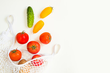Creative natural layout made of tomatoes and cucumbers and leaves on white background. Flat lay. eco bag