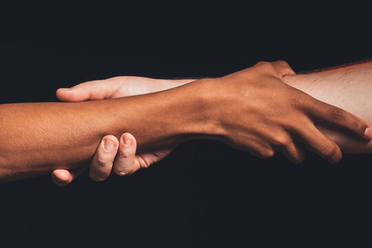 Black lives matter. Peace support. Closeup african caucasian male hands holding together isolated on dark. Racial friendship. Ethnic tolerance. No racism