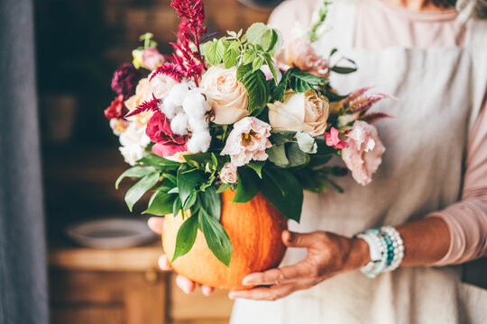 Pumpkin with beautiful bouquet of flowers in woman hands.