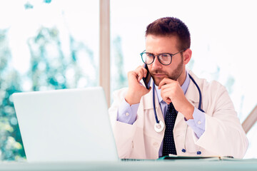 Male doctor using laptop and mobile phone while working in doctor's room