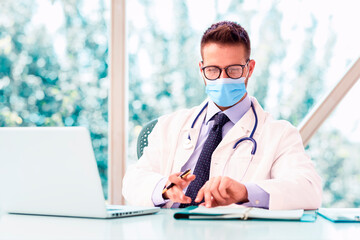 Male doctor wearing face mask while working in doctor's office