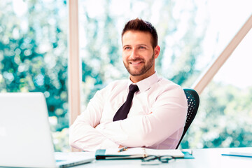 Confident financial businessman working on laptop at office desk