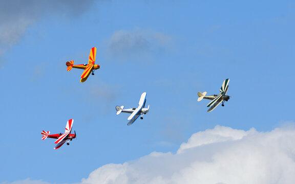 Vintage Tiger Moth Bi Planes Flying in formation blue sky and clouds.