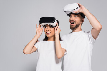 excited interracial couple in white t-shirts touching vr headsets while looking away with open mouths on grey
