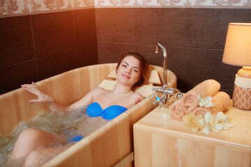 A young beautiful girl relaxes in a wooden hot tub made of wood