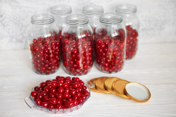 Not closed glass jars with cherries, prepared for canning with tin screw lids