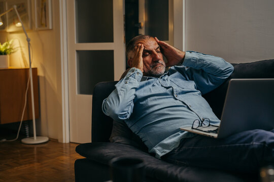 middle aged man sitting sofa having headache while using laptop computer at home