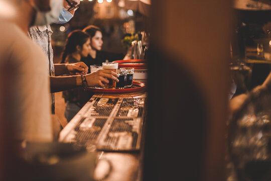 Barista con mascherina di sera serve su vassoio una birra al bancone di un bar in legno all'aperto